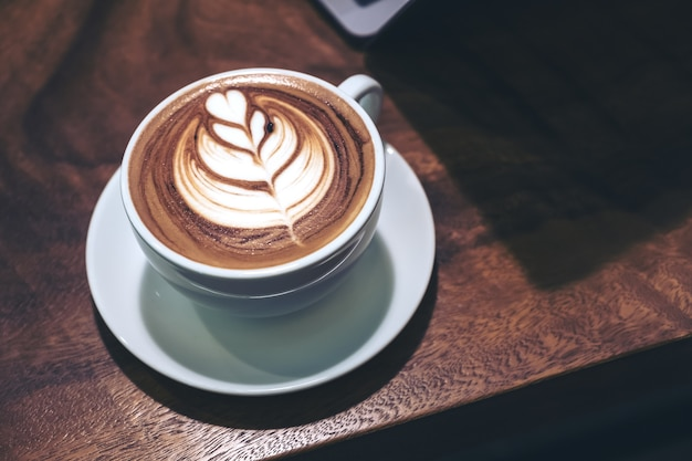 Gros plan image d'une tasse de café au lait chaud avec art de latte de coeur et ordinateur portable