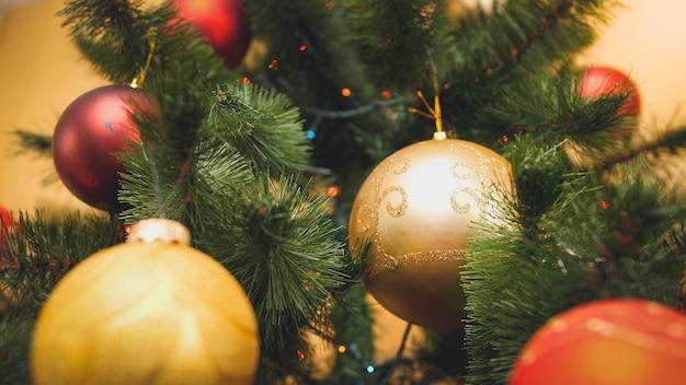 Gros plan de l'image tonique d'une boule étincelante rouge et dorée accrochée à l'arbre de chrismtas. arrière-plan abstrait parfait pour les vacances d'hiver ou les célébrations