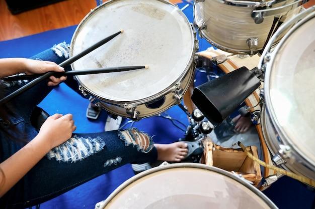 Gros plan des images de fille jouant du tambour.