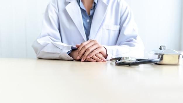 Gros plan des images main de femme médecin posée sur le bureau, aux personnes et au concept de soins de santé.