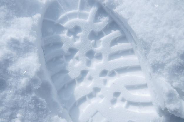 Gros plan de l'impression de chaussures dans la neige, vue aérienne