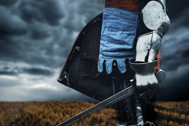 Gros plan de l'incognito tenant l'épée et le bouclier
