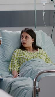 Gros plan sur une infirmière afro-américaine expliquant la radiographie des os surveillant la récupération chirurgicale. patiente malade assise dans son lit discutant d'un traitement de réadaptation dans une salle d'hôpital