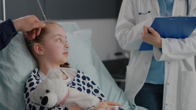 Gros plan d'une infirmière afro-américaine mettant un oxymètre médical sur le doigt de l'enfant