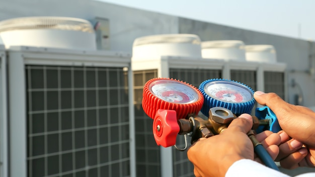Gros plan de l'ingénieur à l'aide de la jauge du collecteur pour le remplissage des climatiseurs.