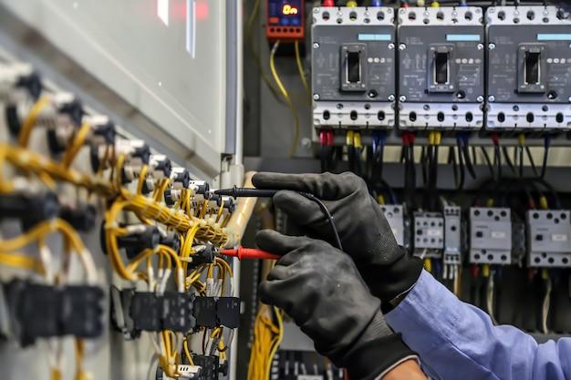 Gros plan de l'ingénieur électricien vérifiant la tension du courant électrique au disjoncteur
