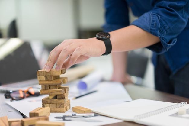 Gros plan ingénieur homme jouant à la main jeu de blocs de bois pour la construction de la tour