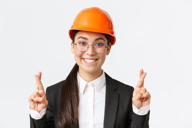 Gros plan d'une ingénieure asiatique pleine d'espoir, d'une directrice de construction en casque de sécurité et d'un costume d'affaires plaidant pour la délectation, croisez les doigts bonne chance et lèvre mordante tentante, fond blanc