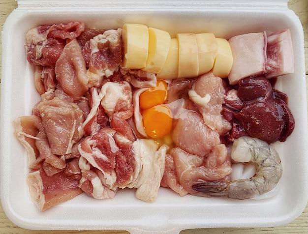 Gros plan d'ingrédients crus frais pour le barbecue de style thaïlandais (moo kratha), tranché diverses parties de porc, de foie, de crevettes, d'œufs et de tofu dans un récipient