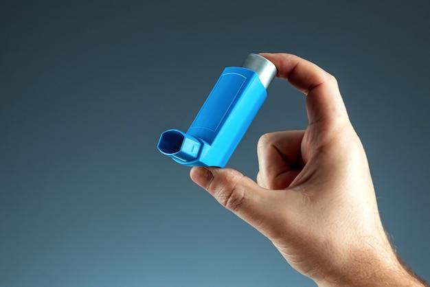 Gros plan avec un inhalateur pour l'asthme dans une main masculine, crise d'asthme. le concept de traitement de l'asthme bronchique, de la toux, des allergies, de la dyspnée.