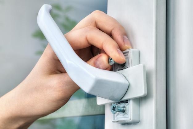 Gros plan de l'installateur manuel, dévissant les vis de fixation de la poignée de fenêtre, à l'aide de ses doigts.