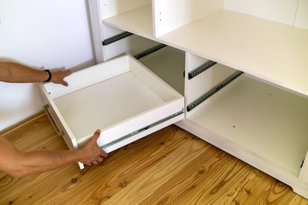 Gros plan sur l'installation d'un tiroir en bois dans une armoire contemporaine.