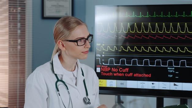 Gros plan, intelligent, femme, cardiologue, laboratoire, blouse, discuter, ecg, données, collègue