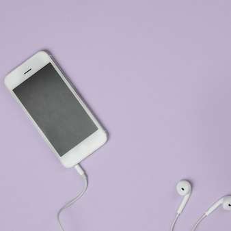Gros plan, intelligent, téléphone, écouteurs, fond (vue de dessus). écoutez de la musique.