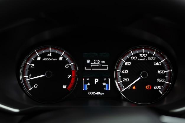 Gros plan intérieur du tableau de bord de voiture kilométrage moderne avec feux d'avertissement, ceintures de sécurité et feux de frein à main