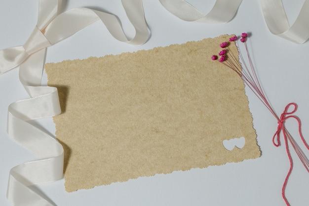 Gros plan d'une invitation de mariage vierge à côté d'un ruban et de petites fleurs rouges sur une surface blanche