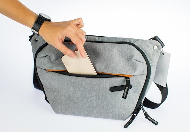 Gros plan isolé, prise de vue en studio d'une femme à la main, ramassant un smartphone de couleur or dans la poche du compartiment d'un petit sac à main gris à glissière avec une longue sangle ou un sac banane devant un fond blanc.