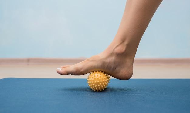 Gros plan d'une jambe faisant rouler une balle de massage jaune sur un tapis
