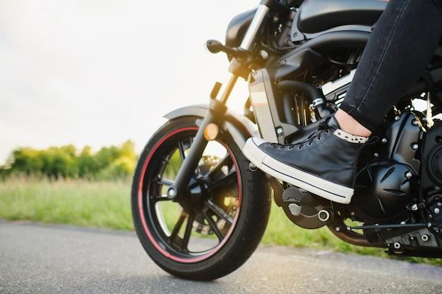 Gros plan sur la jambe d'une femme sur la pédale d'une moto