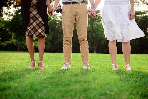 Gros plan des jambes d'amis en keds sur l'herbe.