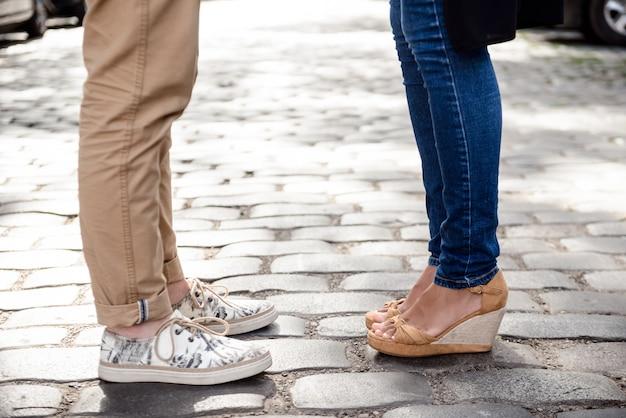 Gros plan des jambes du couple en keds debout dans la rue.