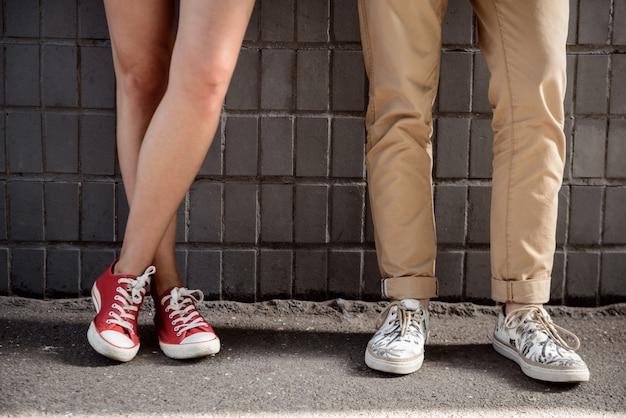 Gros plan des jambes du couple en keds sur mur gris.