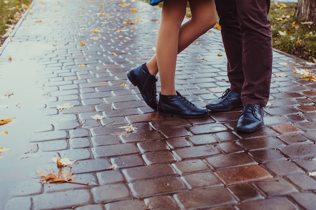 Gros plan des jambes du couple qui s'embrasse en jour d'automne pluvieux