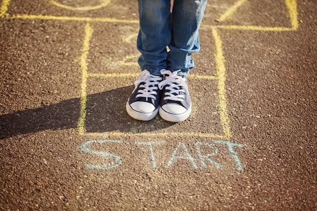 Gros plan des jambes du garçon et jouer à la marelle sur l'aire de jeux en plein air. jeu de rue populaire de la marelle