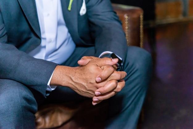 Gros plan des jambes du marié assis sur la chaise et en attente de la cérémonie