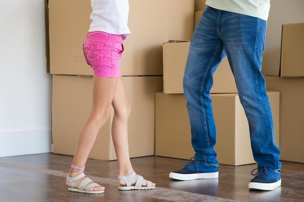 Gros plan des jambes du père et de la fille debout parmi les boîtes en carton dans la nouvelle maison