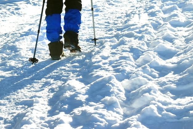 Gros plan sur les jambes du randonneur allant dans les montagnes d'hiver.