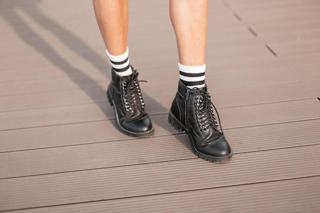 Gros plan des jambes féminines en chaussettes à rayures blanches vintage dans des bottes élégantes en cuir. une femme à la mode marche dans la rue. style rétro.