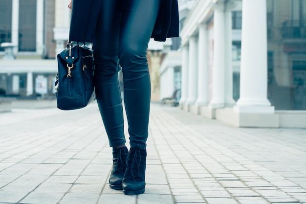 Gros plan des jambes féminines en pantalon noir et bottes