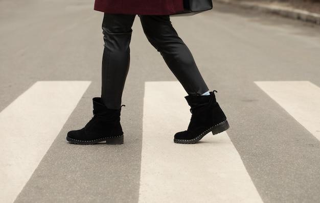 Gros plan des jambes de femme marchant sur le passage pour piétons.
