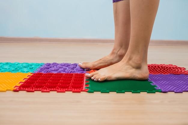 Gros plan des jambes d'une femme marchant sur un tapis orthopédique