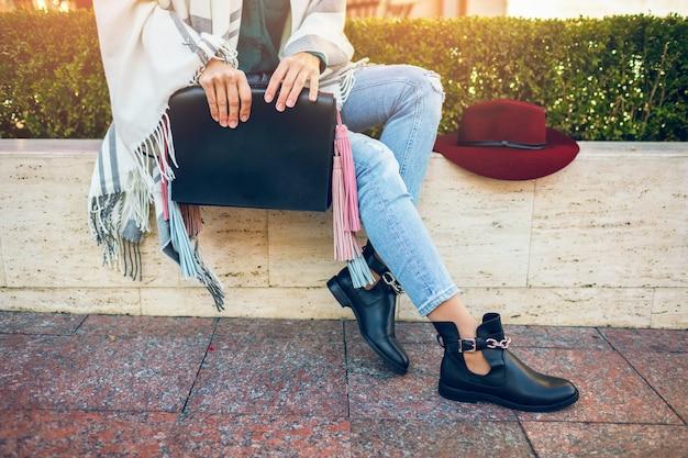 Gros plan des jambes de femme portant des bottes en cuir noir, des jeans, des tendances de printemps de chaussures, sac de tenue