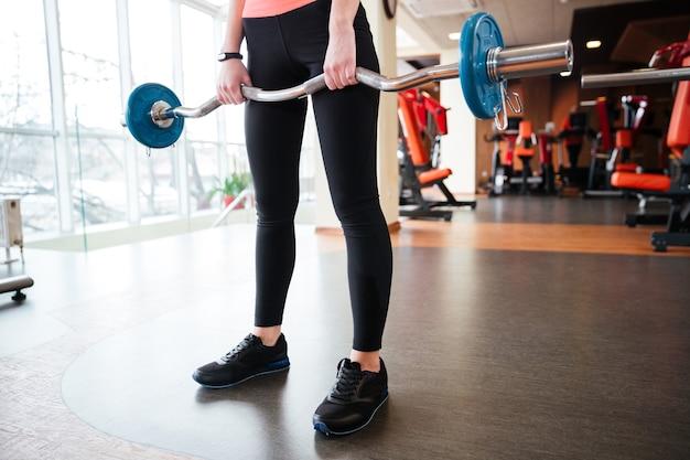 Gros plan des jambes d'une jeune athlète debout et s'exerçant avec des haltères en salle de sport