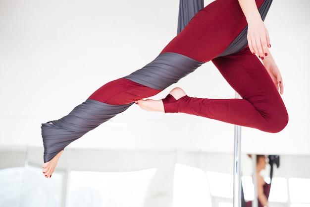 Gros plan des jambes de la jeune femme en leggins pratiquant le yoga aérien en studio