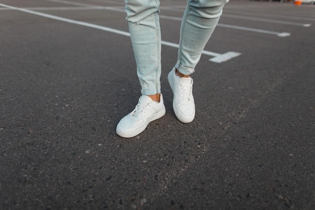 Gros plan des jambes mâles. tendance jeune homme à la mode en jeans bleu vintage en cuir élégantes baskets blanches se tiennent sur la route goudronnée à l'extérieur. style de rue moderne pour les jeunes.