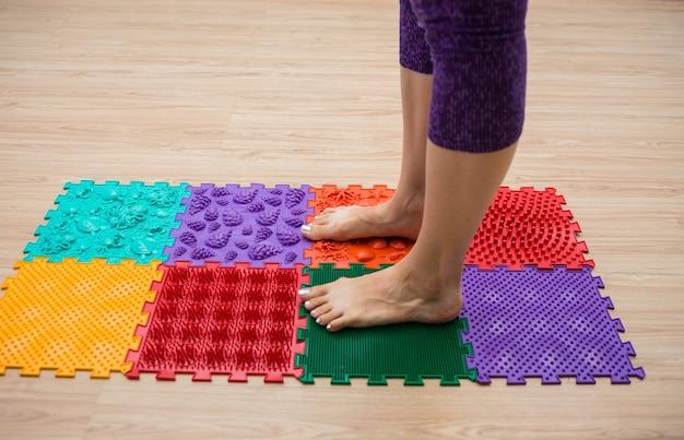Gros plan sur les jambes d'une personne marchant sur un tapis orthopédique