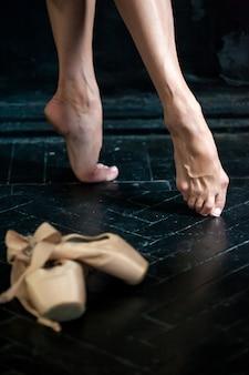 Gros plan des jambes et des pointes de ballerine sur le plancher en bois noir