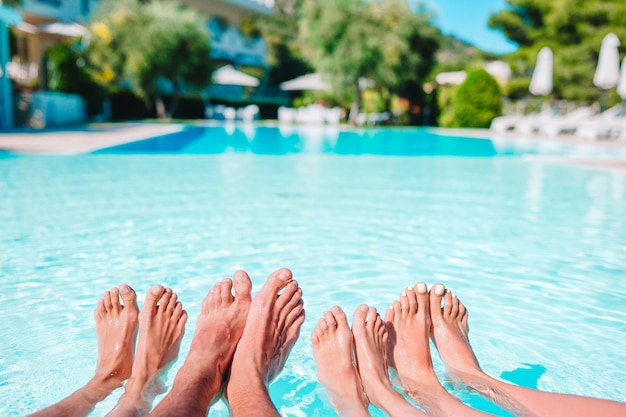 Gros plan des jambes de quatre personnes au bord de la piscine