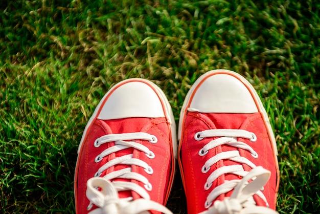 Gros plan des jambes en rouge keds couché sur l'herbe.