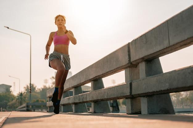 Gros plan des jambesfemmes asiatiques faisant du jogging dans l'entraînement du matin à la ville une ville qui vit en bonne santé