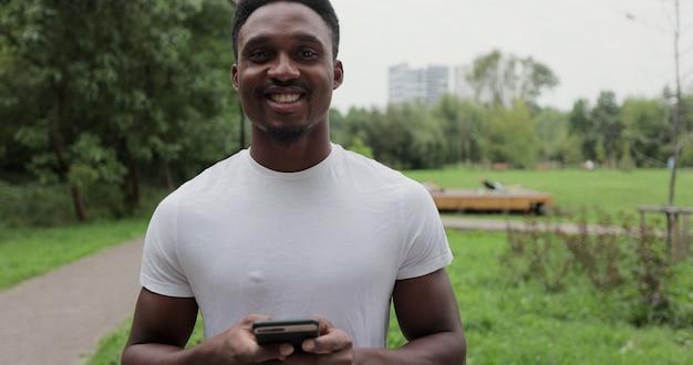 Gros plan sur un jeune afro-américain utilisant un téléphone souriant après une course matinale en regardant un smartphone, un jogger d'entraînement de coureur d'été, un sport de repos.