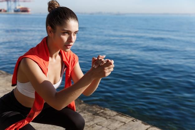 Gros plan d'une jeune athlète féminine concentrée sur une jetée, faisant des squats et regardant la mer.