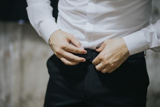 Gros plan d'un jeune et beau marié s'habillant.