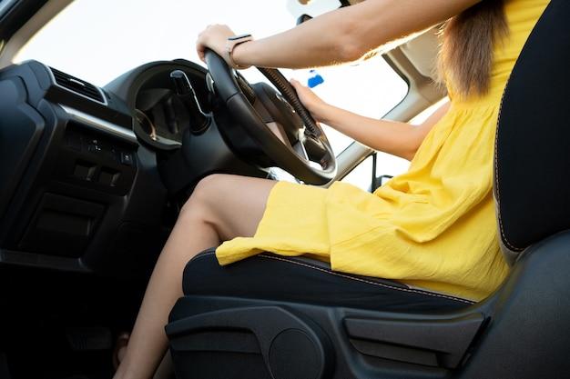 Gros plan sur une jeune conductrice aux longues jambes en robe d'été jaune derrière le volant au volant d'une voiture.
