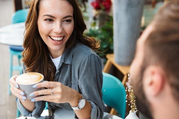 Gros plan d'un jeune couple amoureux en train de déjeuner assis à la table du café à l'extérieur, buvant du café, parlant