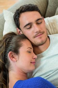 Gros plan, de, jeune couple, délassant, ensemble, sur, sofa, dans, salon